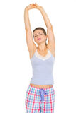 Young woman in pajamas stretching after sleep Royalty Free Stock Images