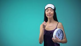 Young woman in pajamas yawning and stretching with clock in hands late awakening. Stock footage stock video