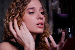 Young woman with palm mirror. Young woman with blusher and a hand-mirror adjusts her make-up Royalty Free Stock Image
