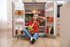Young woman with paper bag full of food sitting near refrigerator. In kitchen stock photo