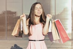 Young woman with paper bags. A young woman with paper bags after shopping standing outside and smiles. She raised her arms to shoulders. Closed eyes. In the Stock Image