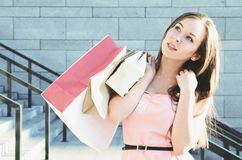 A young woman with paper bags after shopping. Was thinking of standing outside Stock Photography