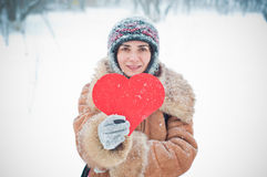 Young woman with a paper heart in the snow Royalty Free Stock Photography
