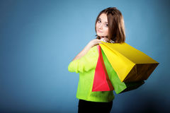 Young woman with paper multi coloured shopping bag Royalty Free Stock Images