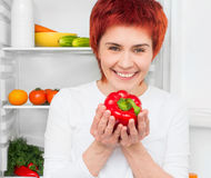 Woman against the refrigerator Royalty Free Stock Images