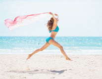 Young woman with parero jumping on beach Stock Image