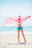 Young woman with parero rejoicing on beach. rear view Royalty Free Stock Images