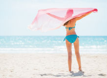 Young woman with parero rejoicing on beach. rear view Stock Photography