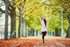 Young woman in Paris by fall. Beautiful young woman in Paris walking in park on a bright fall day, throwing the leaves. Tourism and vacation in France at autumn royalty free stock photo