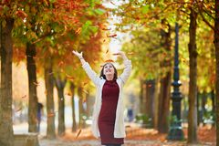 Young woman in Paris by fall. Beautiful young woman in Paris walking in park on a bright fall day, throwing the leaves. Tourism and vacation in France at autumn royalty free stock photos