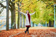 Young woman in Paris by fall. Beautiful young woman in Paris walking in park on a bright fall day, throwing the leaves. Tourism and vacation in France at autumn stock photos