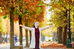 Young woman in Paris by fall. Beautiful young woman in Paris walking in park on a bright fall day, throwing the leaves. Tourism and vacation in France at autumn royalty free stock image