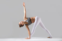 Young woman in Parivrrta Trikonasana pose, grey studio backgroun. Young attractive woman practicing yoga, standing in Revolved Triangle exercise, Parivrrta Royalty Free Stock Images