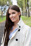 Young woman in park. Portrait a beautiful young caucasian woman in the autumnal park Royalty Free Stock Images