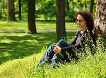 Young woman in the park. Young woman relaxes in the park Stock Image