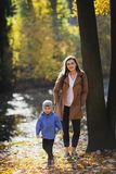 Young woman in the park in autumn with a child. mother with son. Young women in the park in autumn with a child. mother with son. sun royalty free stock images