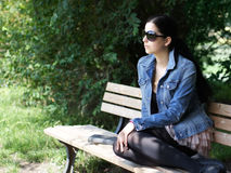 Young woman on park bench Royalty Free Stock Photos