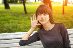 Young woman in Park holding a hand near your ear, the concept of eavesdropping.  royalty free stock image