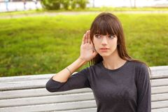 Young woman in Park holding a hand near your ear, the concept of eavesdropping.  stock photography