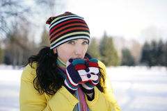 Young Woman in park Holding Mug. Girl in a yellow jacket in the winter in the park drinking from red cups Stock Photos