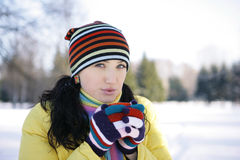 Young Woman in park Holding Mug. Girl in a yellow jacket in the winter in the park drinking from red cups Stock Photo