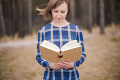 Young woman in the park holding open book Royalty Free Stock Image