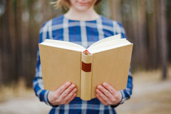 Young woman in the park holding open book Stock Photos