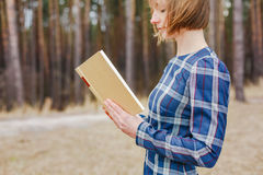 Young woman in the park holding open book Royalty Free Stock Photos