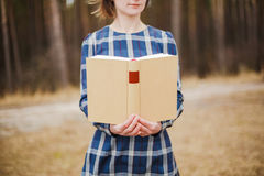 Young woman in the park holding open book Stock Photography
