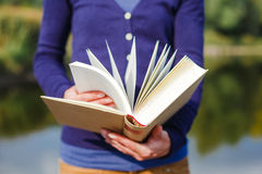 Young woman in the park holding open book Royalty Free Stock Photography