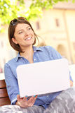 Young woman in the park with laptop Stock Image