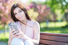 Young woman in the park listening to music Stock Images