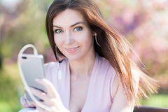 Young woman in the park listening to music Royalty Free Stock Photography