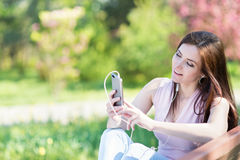 Young woman in the park listening to music Royalty Free Stock Photo