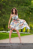 A young woman in the Park playing with the hem of her dress Royalty Free Stock Photo