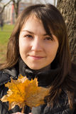 Young woman in the park. Portrait of a young woman holding orange autumn leaf in her hands stock images