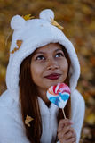 Young woman in park on sunny autumn day, smiling, holding leaves and candy. Cheerful beautiful girl in white sweater Royalty Free Stock Photography