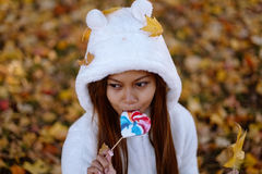 Young woman in park on sunny autumn day, smiling, holding leaves and candy. Cheerful beautiful girl in white sweater Royalty Free Stock Images