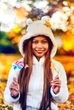 Young woman in the park on sunny autumn day, smiling, holding leaves and candy. Cheerful beautiful girl in white sweater in the pa. Rk with nice colorful royalty free stock images