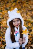 Young woman in the park on sunny autumn day, smiling, holding leaves and candy. Cheerful beautiful girl in white sweater in the pa. Rk with nice colorful stock image