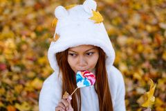 Young woman in the park on sunny autumn day, smiling, holding leaves and candy. Cheerful beautiful girl in white sweater in the pa. Rk with nice colorful stock images
