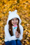 Young woman in the park on sunny autumn day, smiling, holding leaves and candy. Cheerful beautiful girl in white sweater in the pa. Rk with nice colorful stock photos