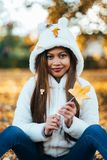 Young woman in park on sunny autumn day, smiling, holding leaves. Cheerful beautiful girl in white sweater.  stock photo