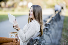 Young woman in park with tablet. Young woman in the park with tablet Stock Image