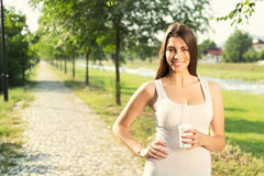 Young woman in park with takeaway coffee Stock Photo