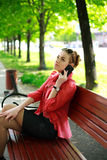 Young woman in a park talking on the phone Stock Image