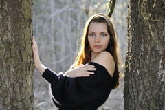 The young woman in park between trees Royalty Free Stock Photos