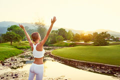 Young woman in the park. Victory and freedom. Enjoying the sun. Morning yoga. Young woman raising hands up in the park against sky Stock Photos