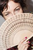 Young woman partly hidden behind a fan Stock Images