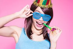 Woman take noisemaker. Young woman with party hat and noisemaker on the pink background stock images